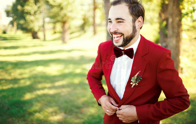 Le marié élégant dans le smoking rit le rouge de marsala de costume, noeud papillon de Bourgogne Homme boutonnant sa veste dehors photos libres de droits