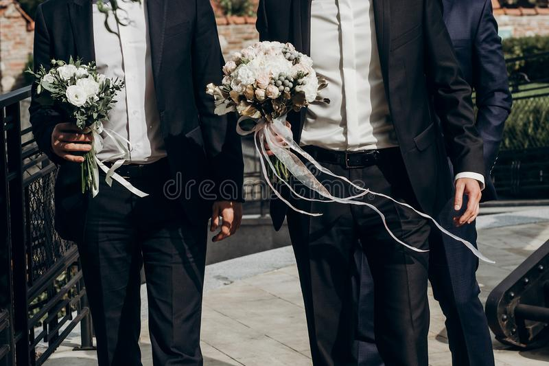 Le marié élégant tenant le bouquet étonnant des roses avec des rubans marchent images stock
