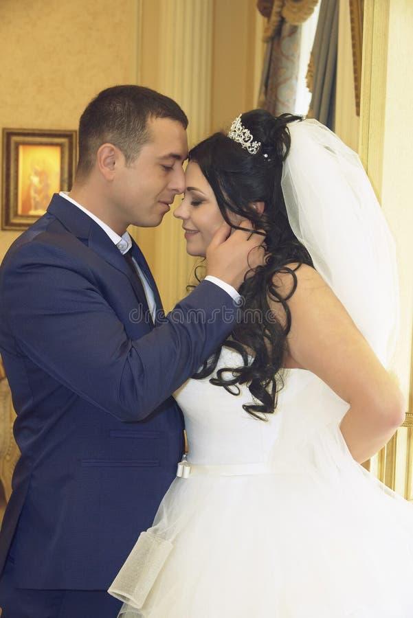 Le marié étreint doucement la jeune mariée images stock