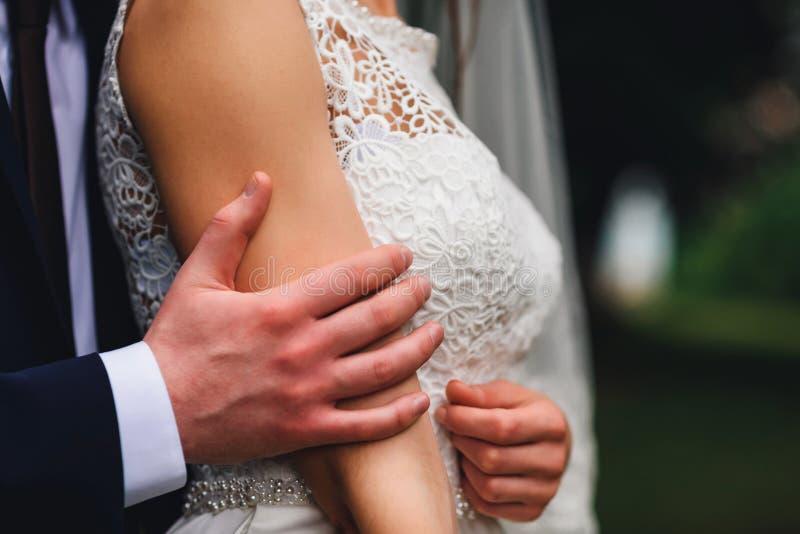 Le marié étreint doucement la jeune mariée le jour du mariage photo stock