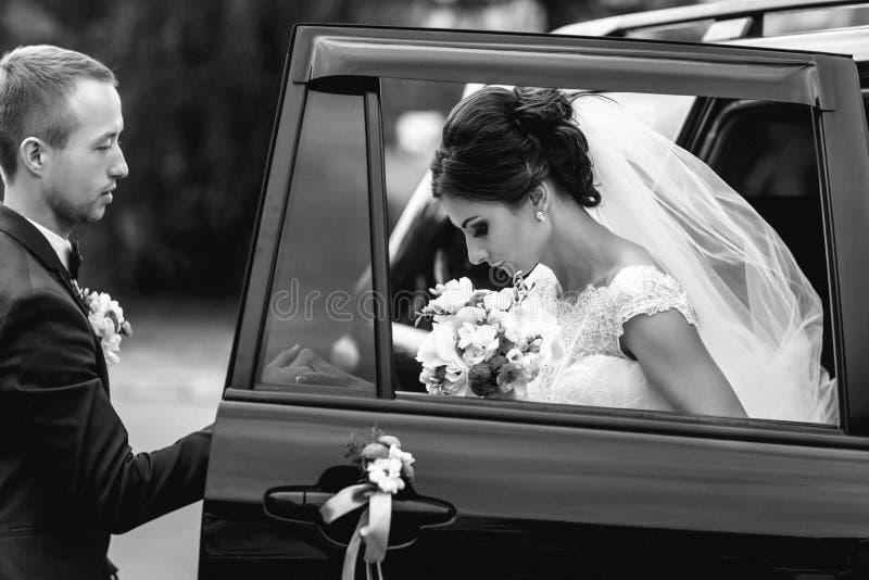 Le marié aide la jeune mariée à faire un pas hors de la voiture noire image stock