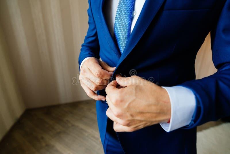 Le marié attache le bouton sur sa veste photo stock
