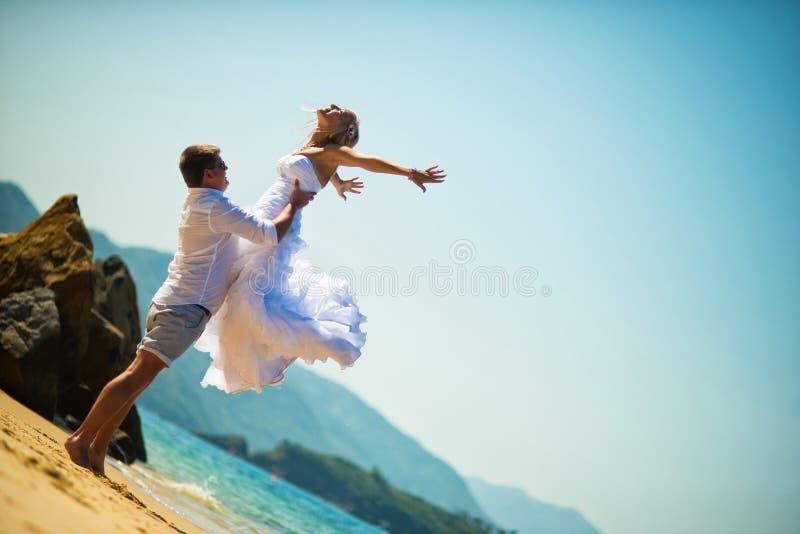 Le marié attrape la jeune mariée dans un saut sur la plage contre la mer un jour ensoleillé d'été photos libres de droits