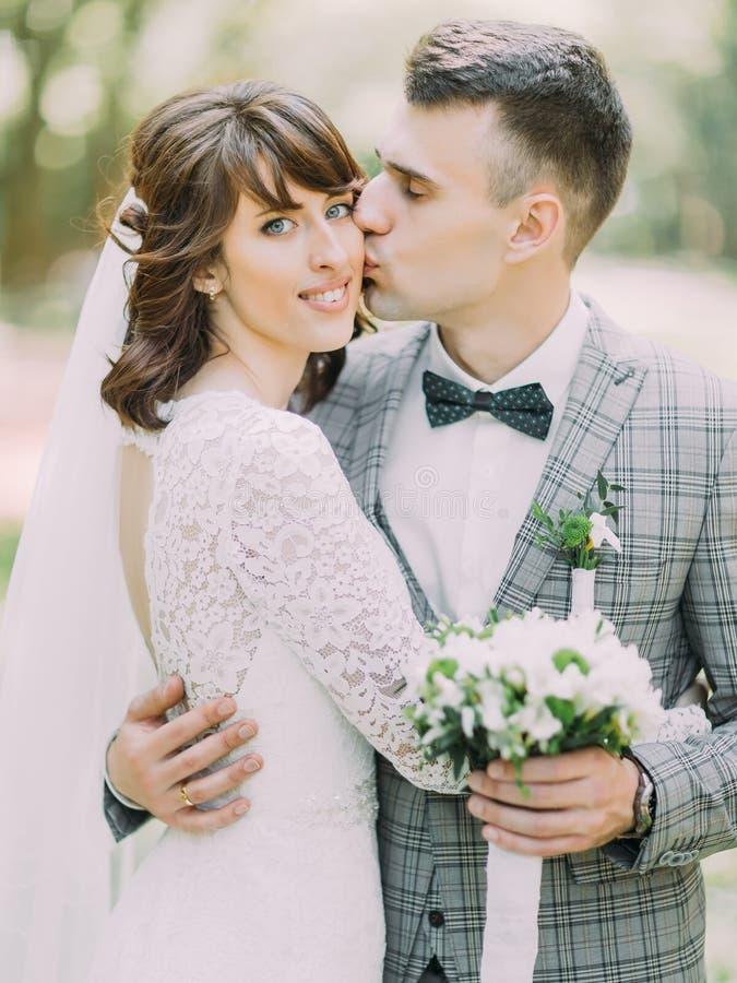 Le marié avec le bouquet de mariage embrasse la jeune mariée gaie dans la joue photos stock