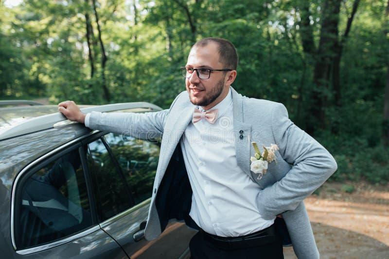 Le marié avec une barbe dans une veste grise et des supports en verre se penchant sur la voiture photos stock