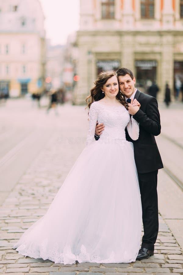 Le marié beau dans le costume noir tient la main de la robe blanche de port de jeune mariée, vieux fond ensoleillé de ville image stock