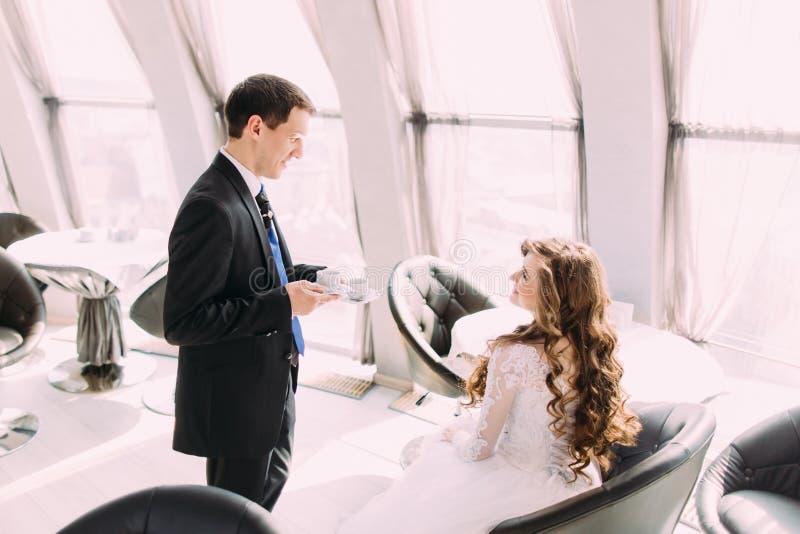 Le marié beau de jeunes dans le costume noir apporte son café de jeune mariée image stock