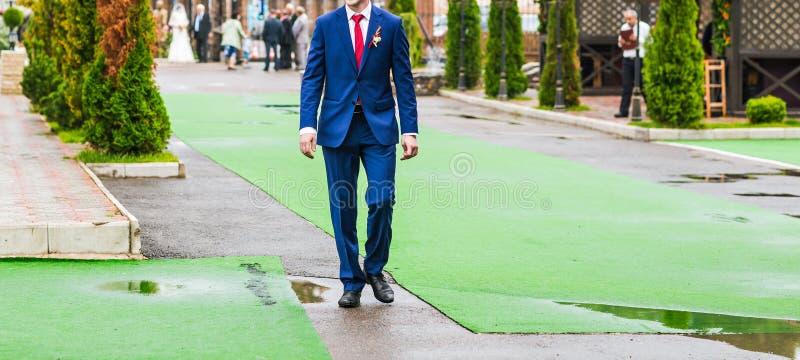 Le marié dans le costume bleu est sur la voie verte à images stock