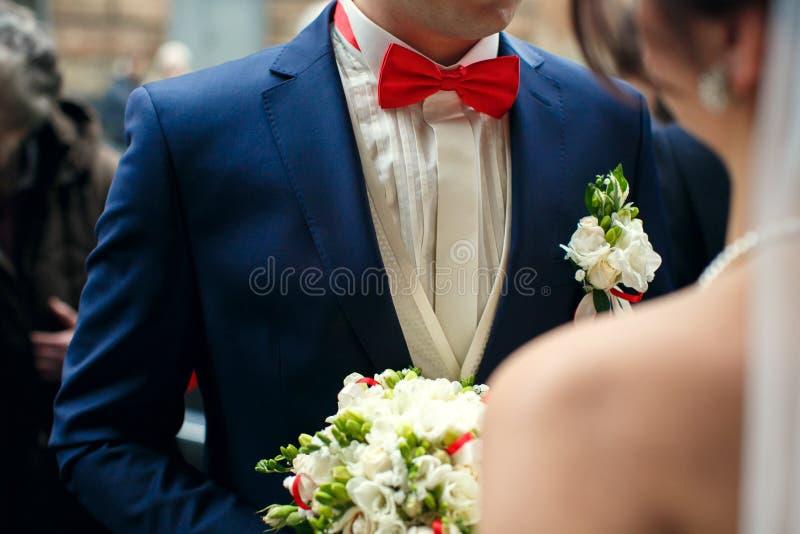 Le marié dans le costume bleu et le noeud papillon rouge se tient dans l'avant d'un brid photographie stock libre de droits