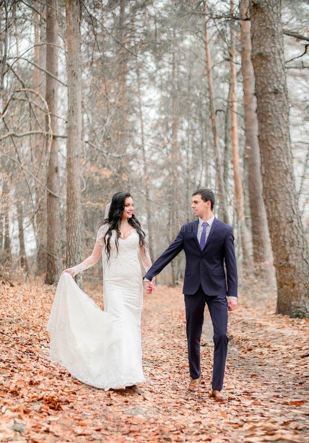 Le marié dans le costume bleu-foncé marche avec une jeune mariée sur les feuilles tombées photos libres de droits