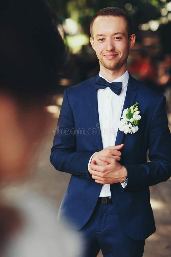 Le marié dans le costume bleu semble heureux admirant une jeune mariée photo stock