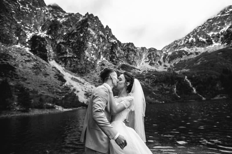 Le marié embrassant sa jeune jeune mariée, sur le rivage du lac Morskie Oko poland P?kin, photo noire et blanche de la Chine image libre de droits