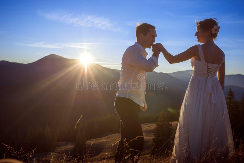 Le marié embrasse la main de la jeune mariée Coucher du soleil dans les montagnes sur le fond photo libre de droits