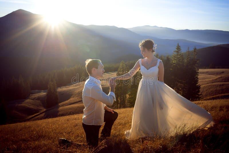 Le marié embrasse la main de la jeune mariée Coucher du soleil dans les montagnes sur le fond photos libres de droits