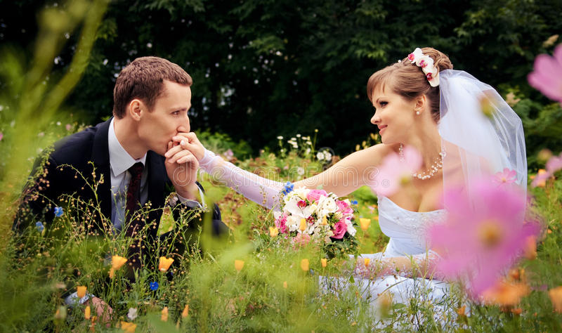 Le marié embrasse la main de la mariée images stock