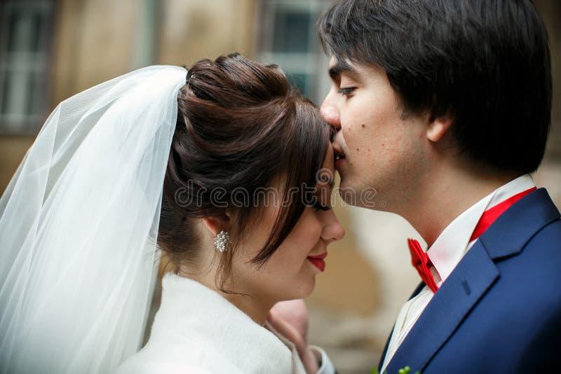 Le marié embrasse le front du ` s de jeune mariée tandis qu'elle se tient avec les yeux fermés images libres de droits