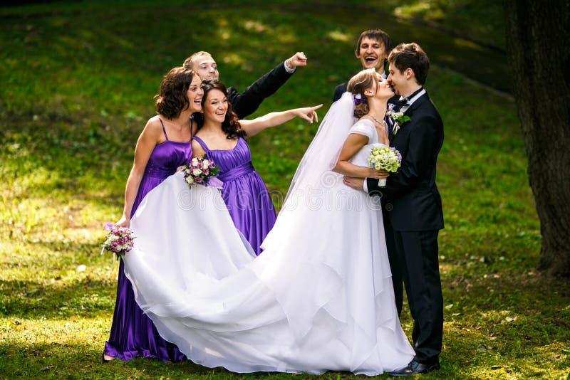Le marié embrasse une jeune mariée tandis que ses amis grimace derrière lui photographie stock