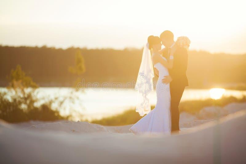 Le marié est tenant et embrassant sa jeune mariée sur le coucher du soleil de fond photos stock