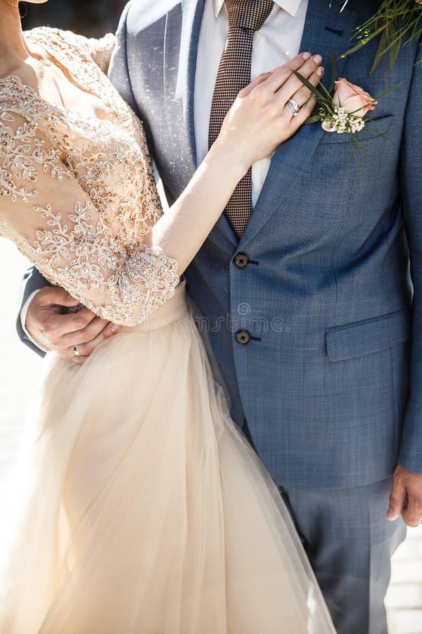 Le marié et la jeune mariée étreignent Les jeunes mariées remettent est sur le coffre de mariés photo libre de droits