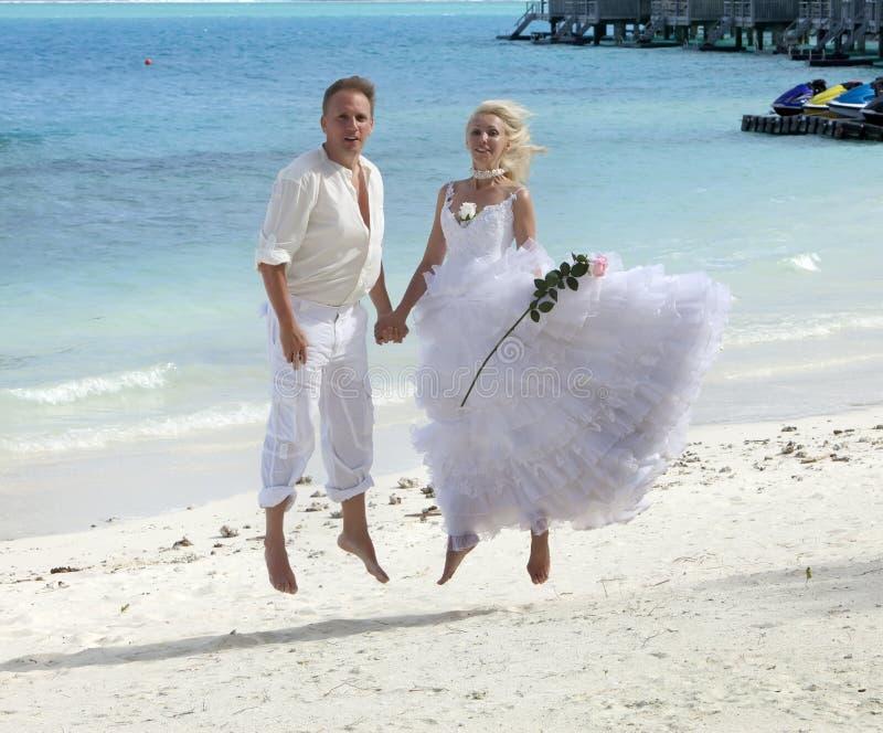 Le marié et la jeune mariée sautent sur la plage tropicale images libres de droits