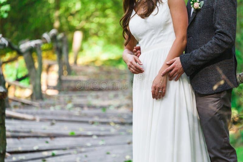 Le marié et la jeune mariée se tiennent en parc d'été, image cultivée image stock