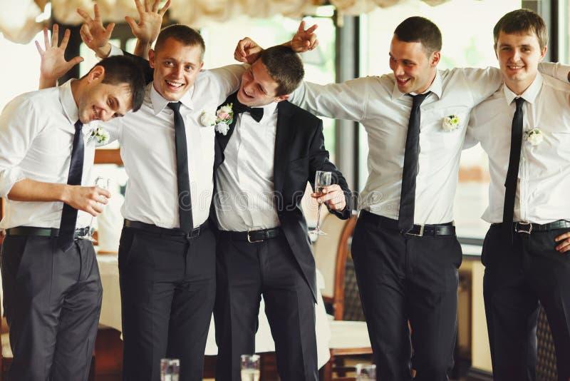 Le marié et les garçons d'honneur ont l'amusement tout en posant dans le restaurant images stock