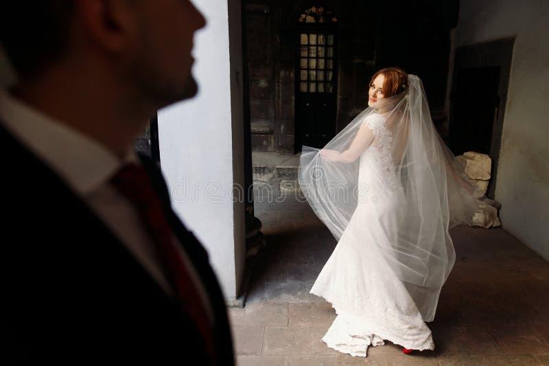 Le marié heureux regarde la belle danse blonde de jeune mariée dans le stree photo libre de droits