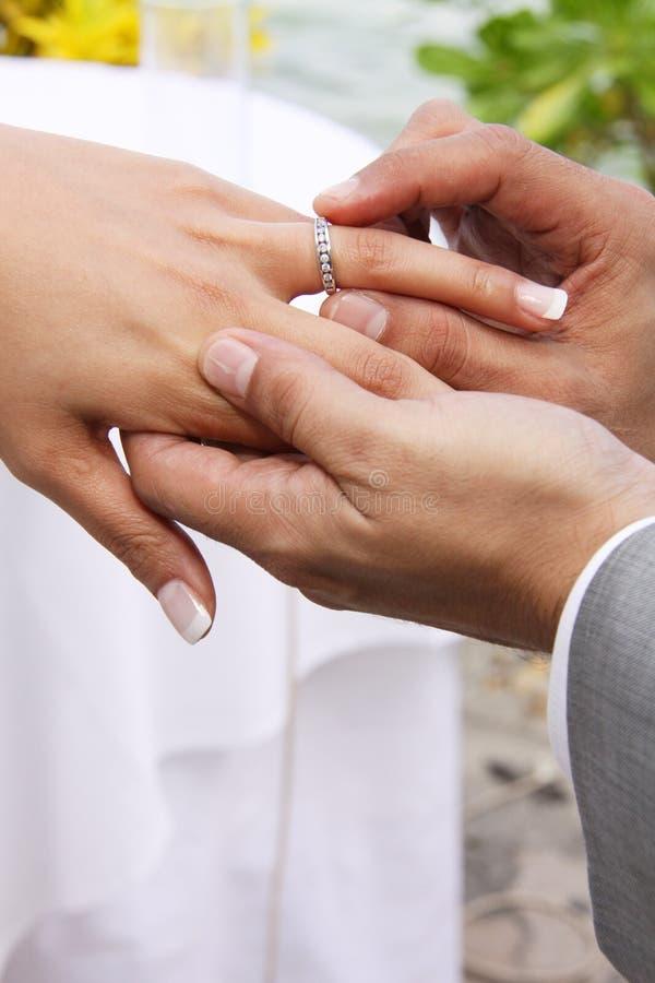 Le marié met la boucle sur la mariée photo stock
