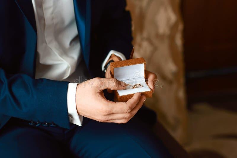 Le marié tient une boîte avec des anneaux de mariage avant la cérémonie l'épousant Les mains des hommes tenant une boîte avec des photographie stock