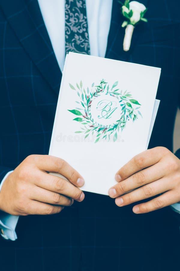 Le marié tient une invitation image stock