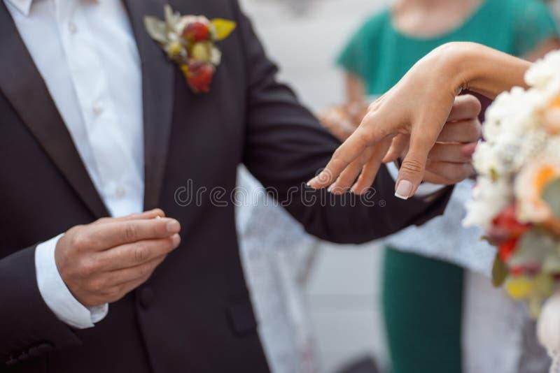 Le marié In une veste bleu-foncé avec un boutonniere met un anneau sur la main de la jeune mariée tir en gros plan de l'emblavage images stock