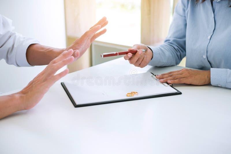 Le mari et l'épouse lisent l'accord de divorce et le stylo de classement à image libre de droits