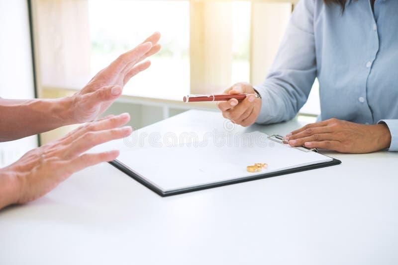 Le mari et l'épouse lisent l'accord de divorce et le stylo de classement à photo stock