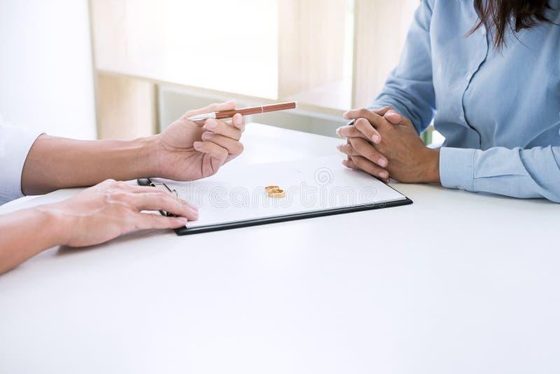 Le mari et l'?pouse lisent l'accord de divorce et le stylo de classement au d?cret de signature de la dissolution de divorce ou d image libre de droits