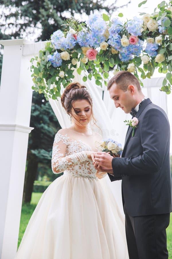 Le mari? porte un anneau sur la main de la jeune mari?e sur la c?r?monie de mariage image libre de droits