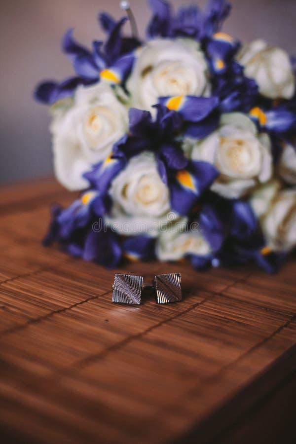 Le mariage détaille les anneaux et le bouquet du ` s de marié sur la table photo stock