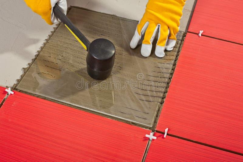 Le marteau en caoutchouc installent les tuiles en verre photos libres de droits