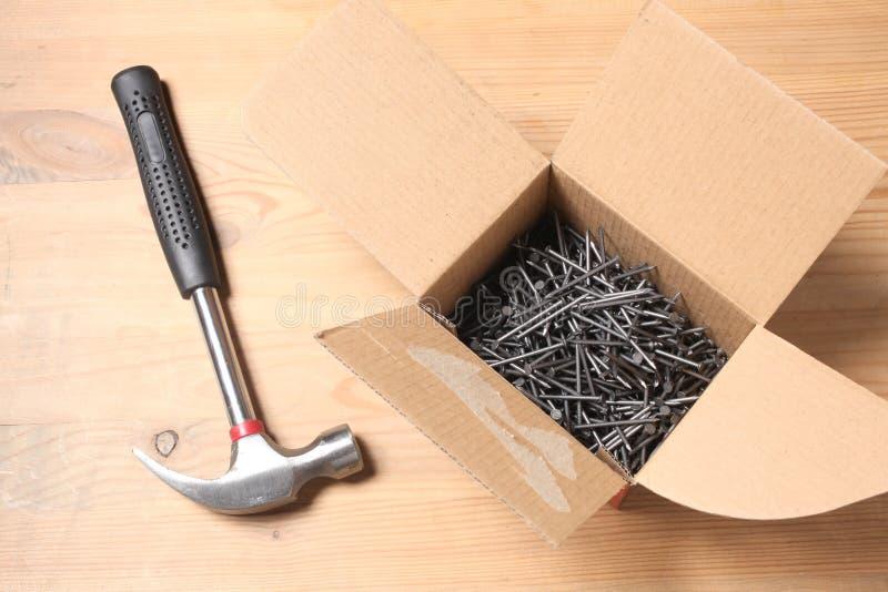 Le marteau et une boîte complètement de clous se reposent sur une table en bois avec l'espace de copie pour votre texte photo stock