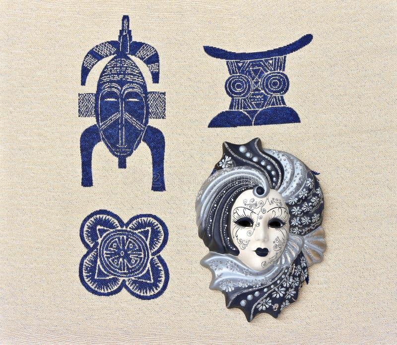 Le masque vénitien est sur le tissu avec des motifs africains photos stock