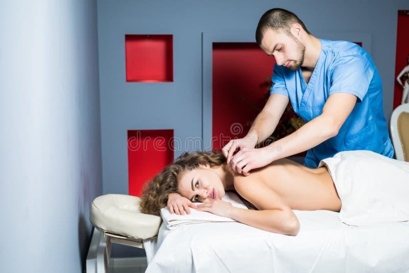 Le massage de détente de jeune femme bouclée de beauté au salon de station thermale de beauté détendent du massage de corps du th photos stock