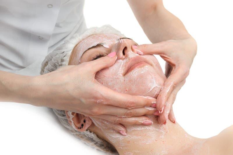 Le massage facial avec frottent le masque images stock