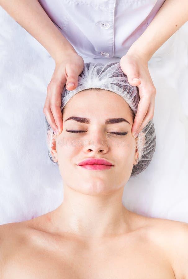 Le massage facial de lymphodrainage professionnel le cosmetologist touche le front du ` s de client Soins de la peau de levage image stock