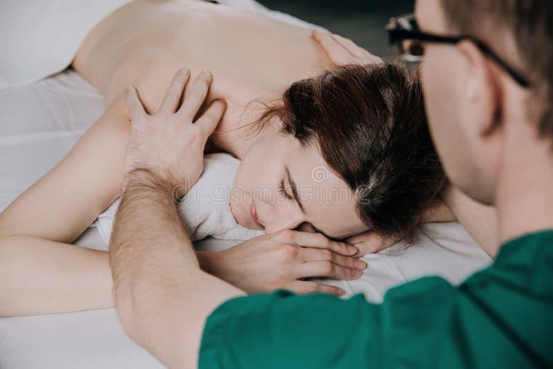 Le masseur masculin fait l'?paule de massage d'une jeune femme Beau visage d?contract? d'une jeune femme avec les cheveux bruns photos stock