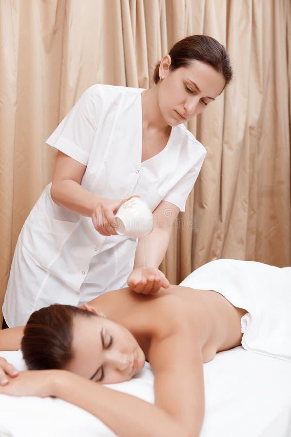 Le masseur masse à une femme image stock