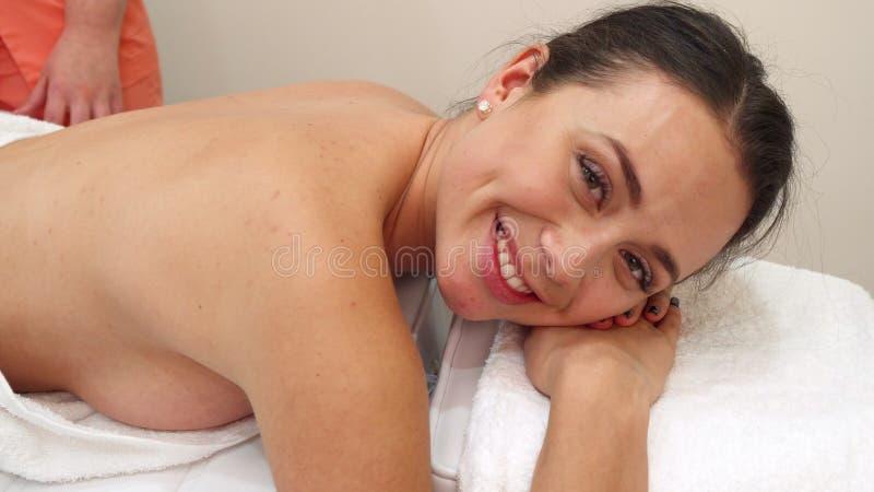 Le masseur masse le dos du ` s de femme image stock