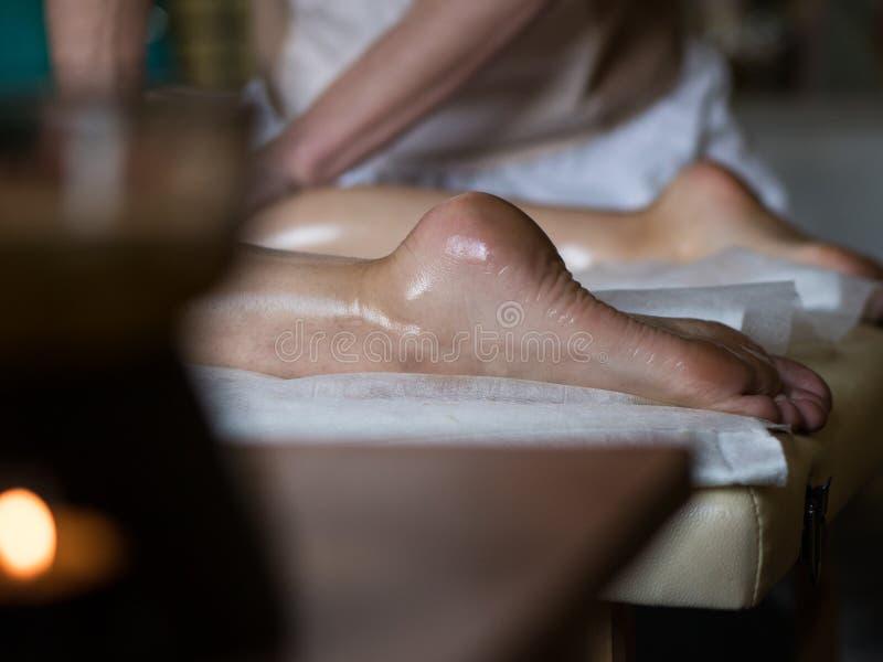 Le masseur professionnel que faire malaxe des jambes d'une fille chez Ayurveda a huilé la session de massage images stock