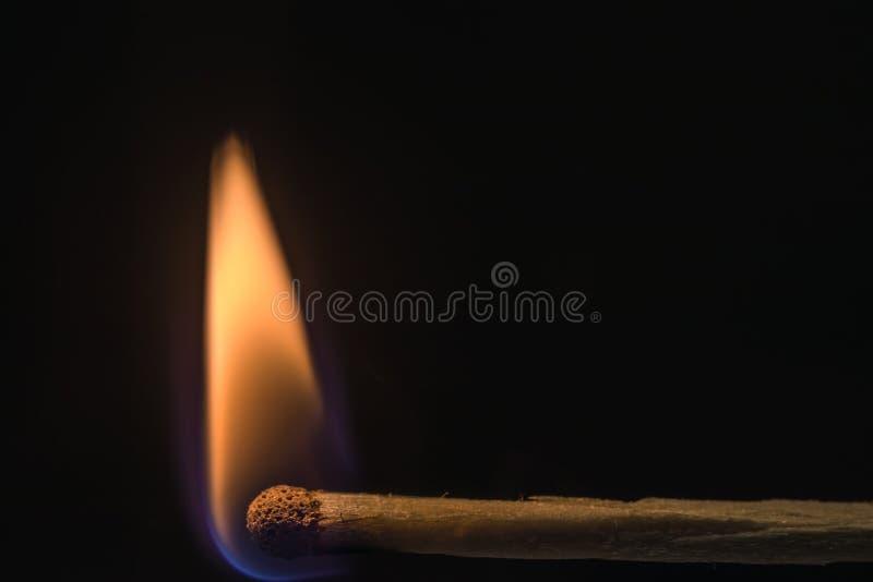 Le match brûle avec une flamme égale sur une obscurité photos libres de droits