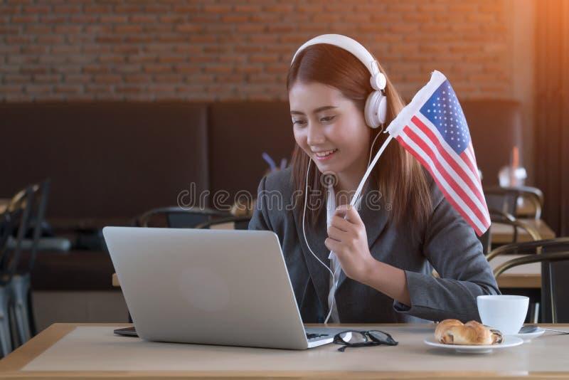 Le match en ligne de écoute de jeune femme d'affaires asiatique, l'acclamation Etats-Unis team image libre de droits