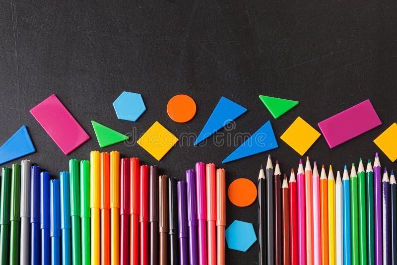 Le matite nella fila e geometrico variopinti dipende la lavagna nera della scuola immagini stock libere da diritti