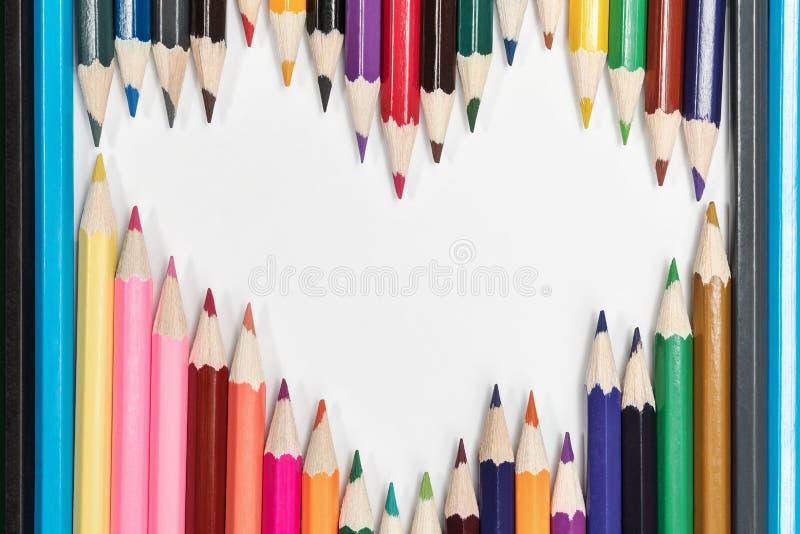 Le matite su Libro Bianco gradiscono un cuore fotografia stock